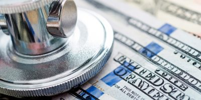 Stethoscope on us paper currency, healthcare costs concept.